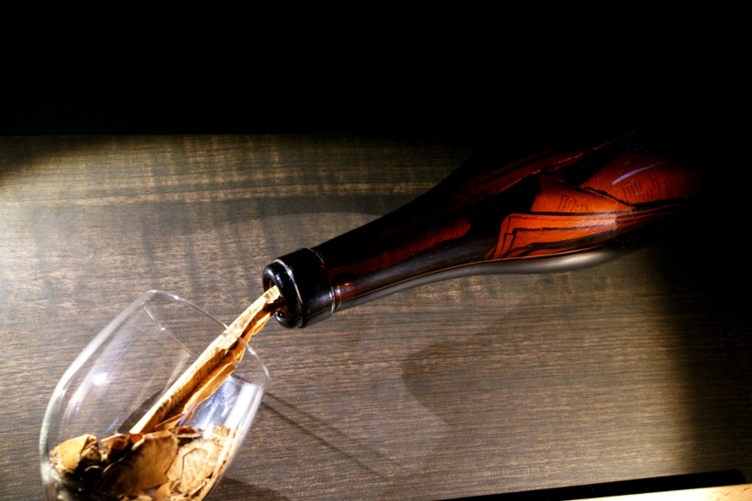 """""""vino: succo di cultura"""" 2014 - bottiglia albesina contenete pagine di un vecchio libro che si riversano in un calice"""